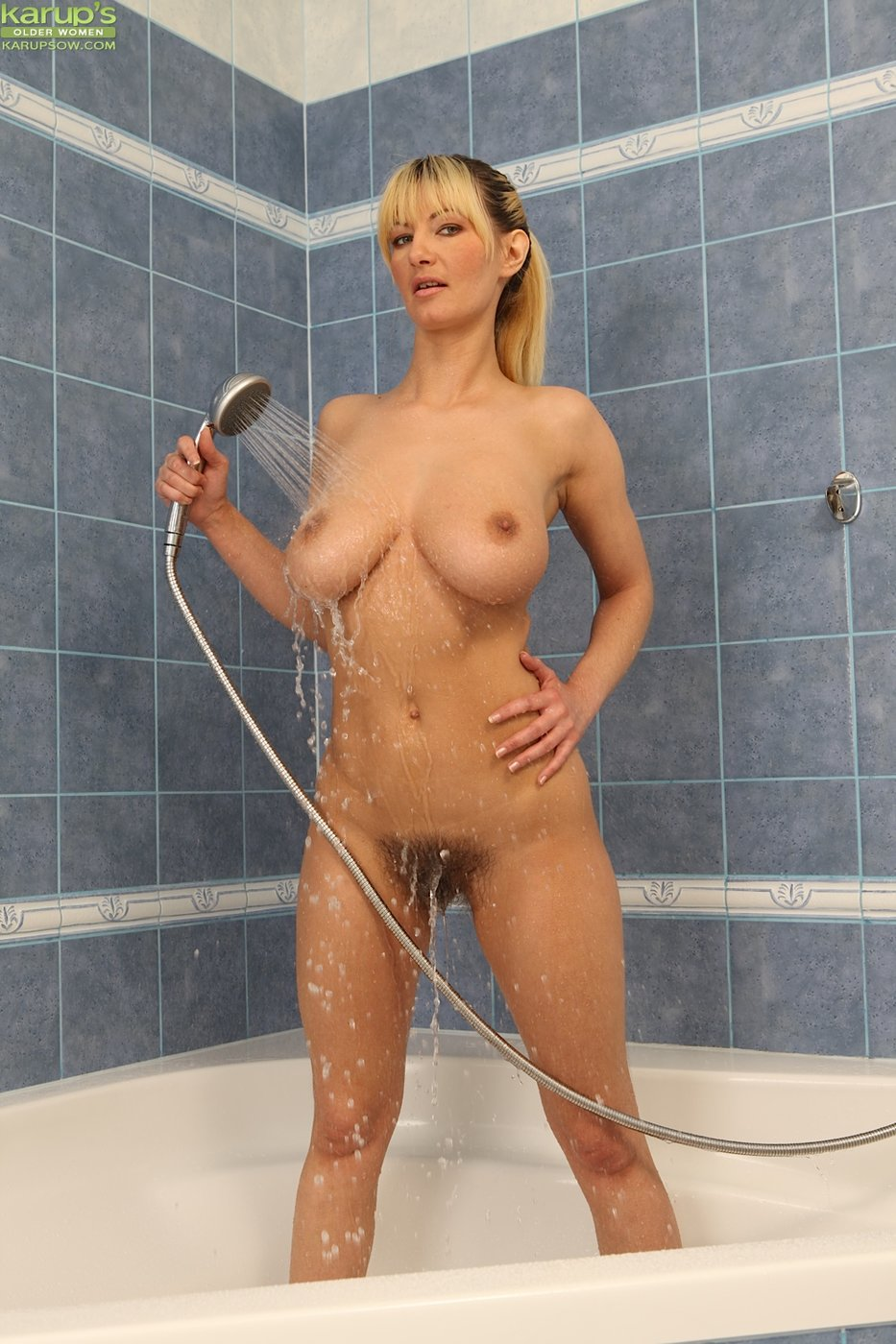 Ponytailed blonde with a hairy pussy masturbating in the bathroom
