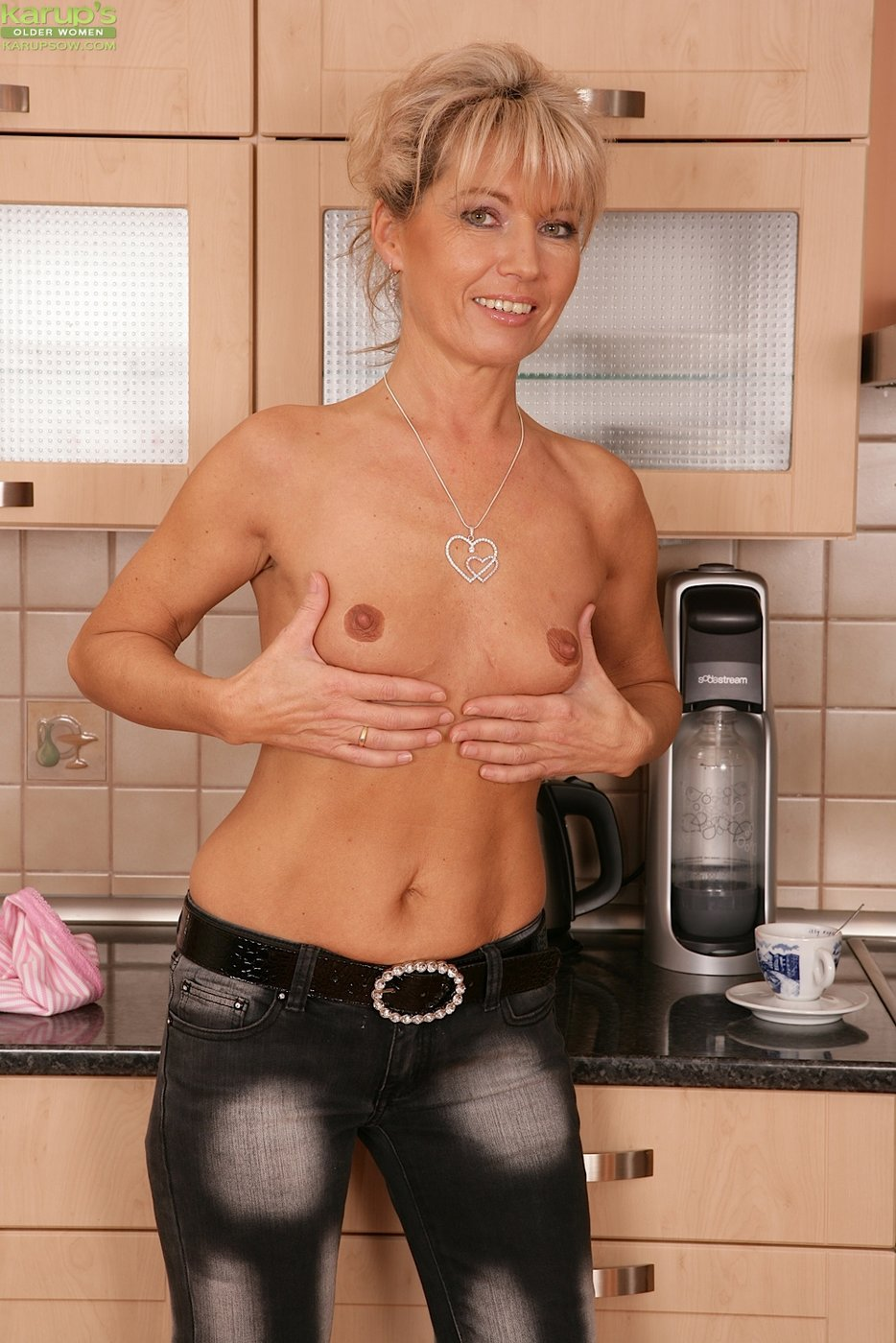 Tanned and skinny MILF teasing her bushy pussy on the kitchen floor
