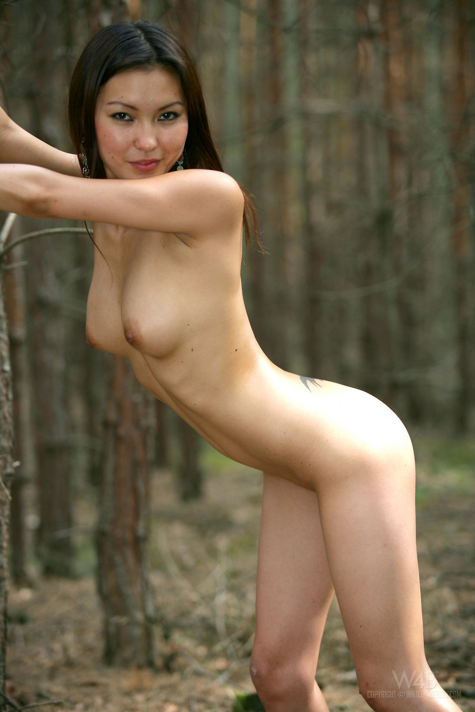 Yellow bikini exotic beauty shows off her naked body in the forest